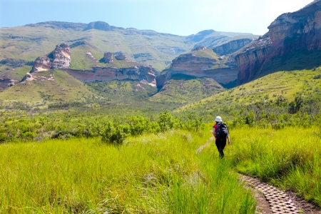 Young female tourist walking mountain trail in highlands.