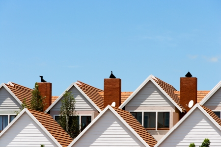 homeownership: Close up detail of town house rooftops with chimneys against blue shy.