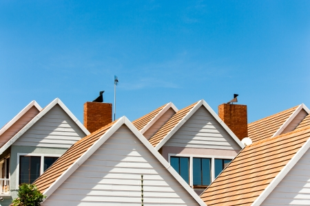 homeownership: Close up detail of complex house rooftops against blue sky. Stock Photo
