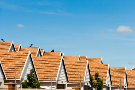 Row of condominium rooftops against blue sky.