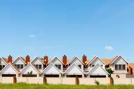 condominium complex: Residential fenced house complex against blue sky.