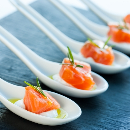 morsels: Numerous porcelain spoons with smoked salmon morsels. Stock Photo