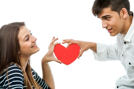 Close up portrait of cute teen couple holding small red heart together.Isolated on white background. photo