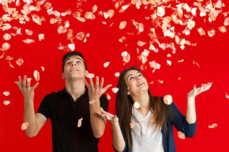 Couple with arms raised having fun throwing rose petals over red background. photo