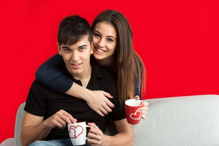 Close up portrait of cute couple drinking coffee together on couch.Isolated on red background. photo