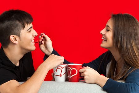first love: Close up portrait of teen couple having great time drinking coffee.Isolated on red background.
