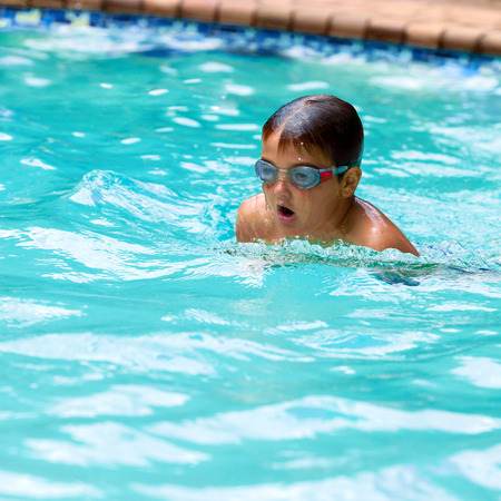 Close up of young boy swimming in outdoor pool.