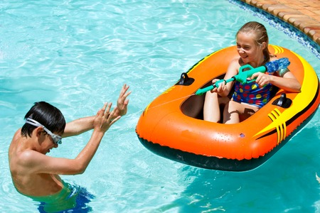 Close up of girl spraying boy with water gun in pool. photo