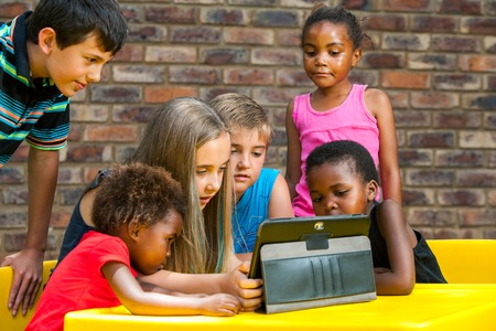 american culture: Multiracial group of children looking at tablet outdoors.