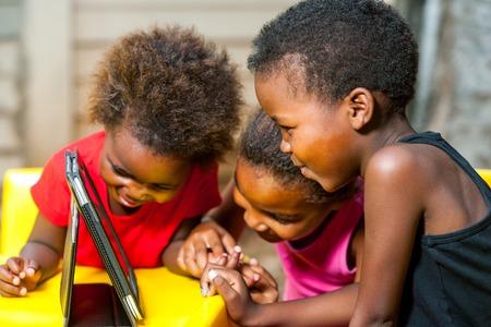 디지털 태블릿에 함께 놀고 세 아프리카 젊은 여자의 초상화를 닫습니다. 스톡 콘텐츠
