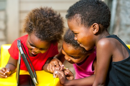 Close up portrait of three african young girls playing together on digital tablet. Stock Photo