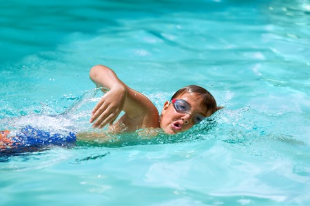 swimming goggles: Close up of young boy at swimming practice outdoors.