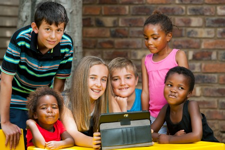 Group of diverse kids playing together on digital tablet outdoors. photo