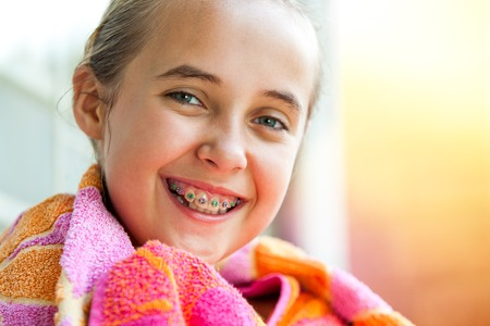 Close up outdoor portrait of cute kid with dental braces smiling.  photo