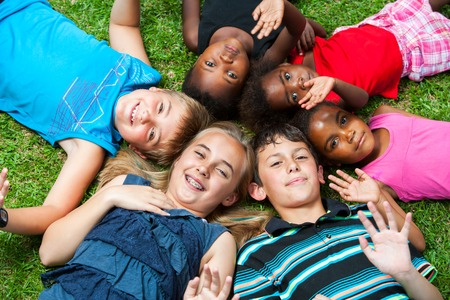 Diverse multiracial group of kids laying together joining heads. Stock Photo