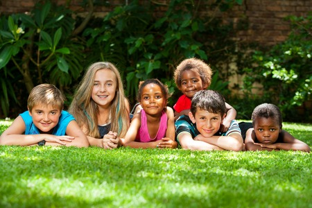 multiracial groups: Diversity portrait of children laying together on grass outdoors.