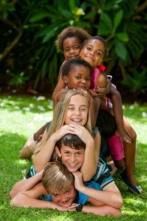 diversidad cultural: Ni�os multirraciales jugando juntos formando pila humana en el jard�n. Foto de archivo