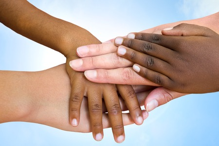 diverse family: Close up of multiethnic childrens hands making pile against blue sky.