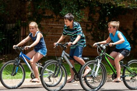 ciclos: Movimiento de tiro de tres kidscompeting con ciclos al aire libre.