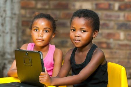 야외에서 디지털 태블릿와 두 아프리카 어린이의 초상화를 닫습니다.
