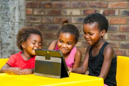 Portrét tří afrických dívek hraní zábavných her na tabletu.