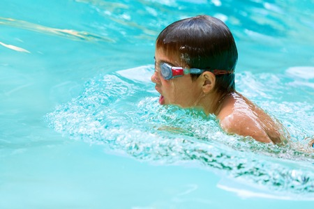 swimming goggles: Close up of young boy swimming in pool. Stock Photo