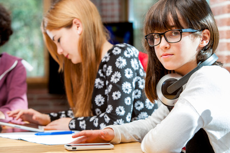 urban environments: Close up portrait of young student together with friends at desk.
