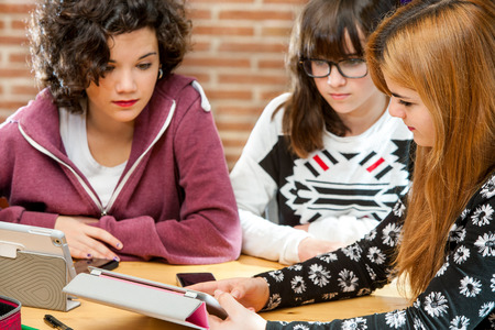Three young attractive female students sharing information on tablet at desk.