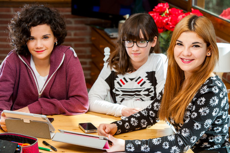 Close up portrait of threesome female students with tablets at desk. photo