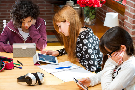digital school: Threesome female students doing tasks on digital devices indoors at desk. Stock Photo