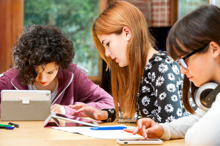 Young girls doing homework together at desk with tablets. photo