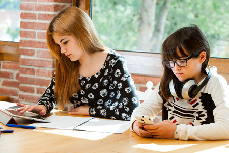 Two young girls concentrating on digital devices at desk. photo