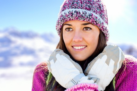 Close up face shot of attractive girl wearing beanie and gloves in snowy mountains  photo