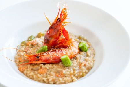 risotto: Close up of seafood risotto dish with red prawns and asparagus.