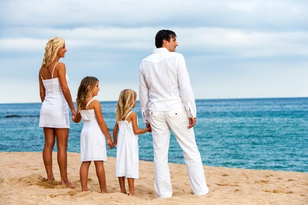 Cute family in white on beach looking into the distance. photo