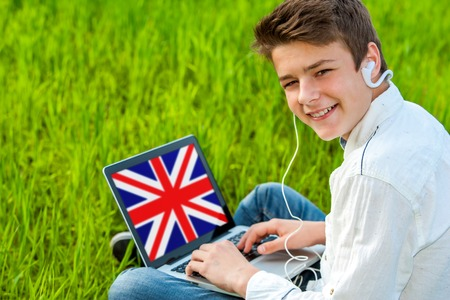 computer language: Portrait of attractive teen boy learning english on laptop outdoors.