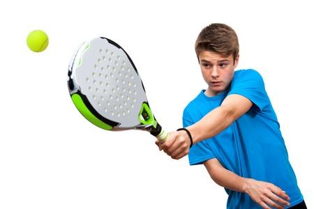 Cierre de jugador de pádel muchacho adolescente en la acción aislada contra el fondo blanco.