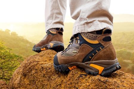 Macro close up of female hiker boots on rocks at sunrise. photo