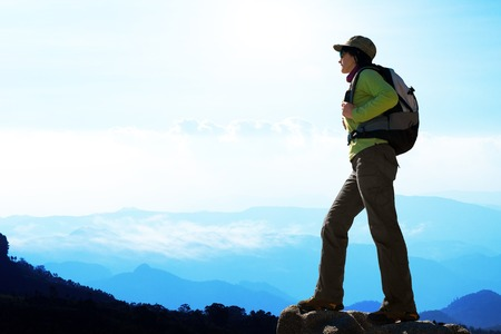 expedition: Silhouette of female hiker against blue mountain scape. Stock Photo