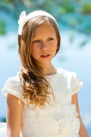 Close up portrait of cute girl in white dress and head band outdoors. Stock Photo