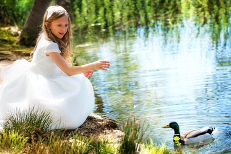 kids dress: Portrait of cute young girl feeding a duck at riverside. Stock Photo