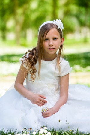 queen of angels: Portrait of cute girl in communion dress holding flowers outdoors.