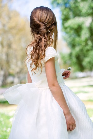 rear view girl: Close up of girl in white dress showing hairstyle outdoors. Stock Photo