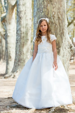 queen of angels: Full length portrait of cute girl in white dress in forest. Stock Photo