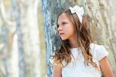 innocent girl: Portrait of young girl in white dress standing next to tree.