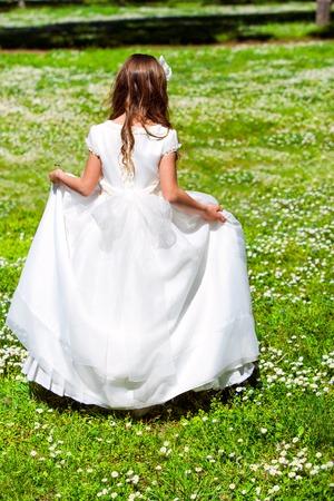 vestido blanco: Ni�a con vestido blanco caminando en campo de flor.