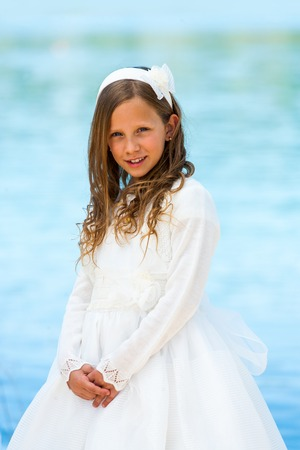 little girl dress: Portrait of cute girl in communion dress with water background.