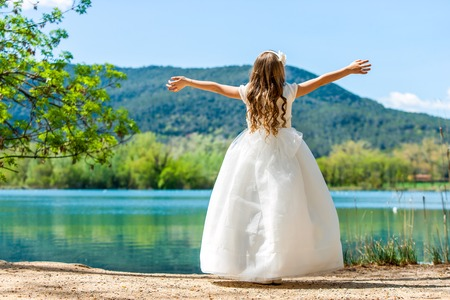 Young girl in white communion dress with open arms at lake. 스톡 콘텐츠