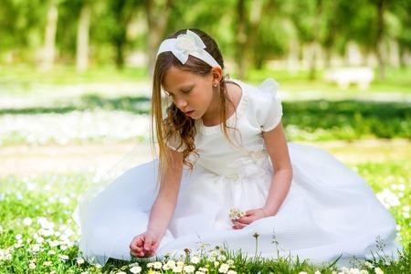 vestido blanco: Retrato de ni�a linda en vestido blanco recogiendo flores en el jard�n.