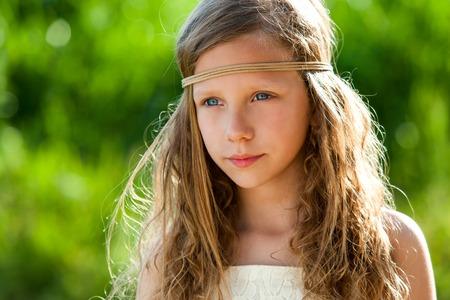 hair band: Portrait of cute girl wearing ribbon headband in green outdoors.